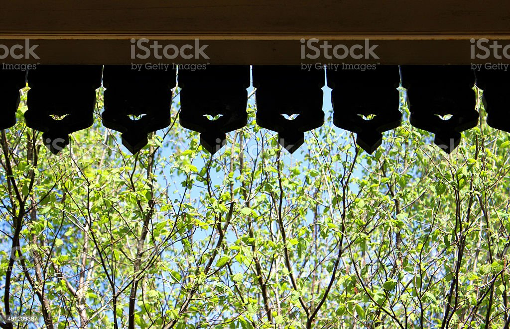 Image of ornate wooden edging to roof against garden background stock photo