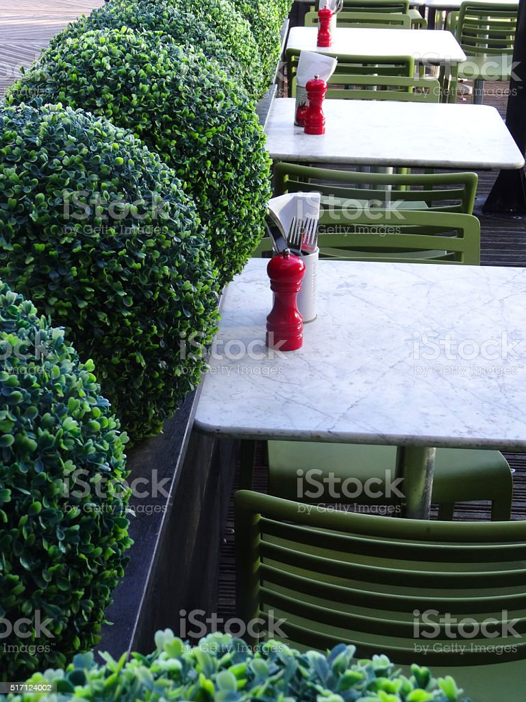 Image of outdoor pavement restaurant tables and chairs, artificial plants stock photo