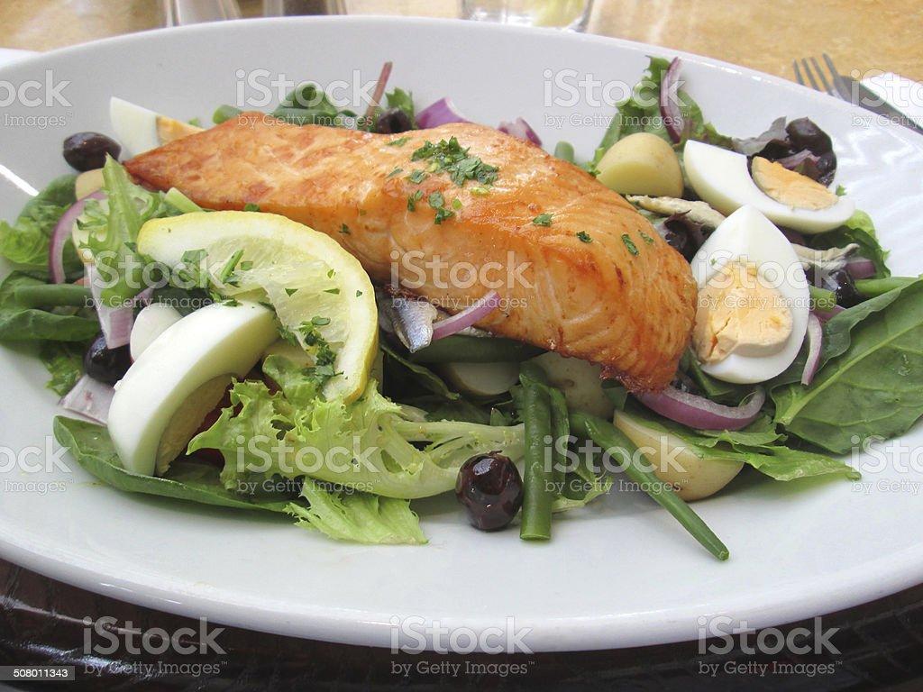 Image of pan fried salmon nicoise dish, salad, eggs, lemon stock photo