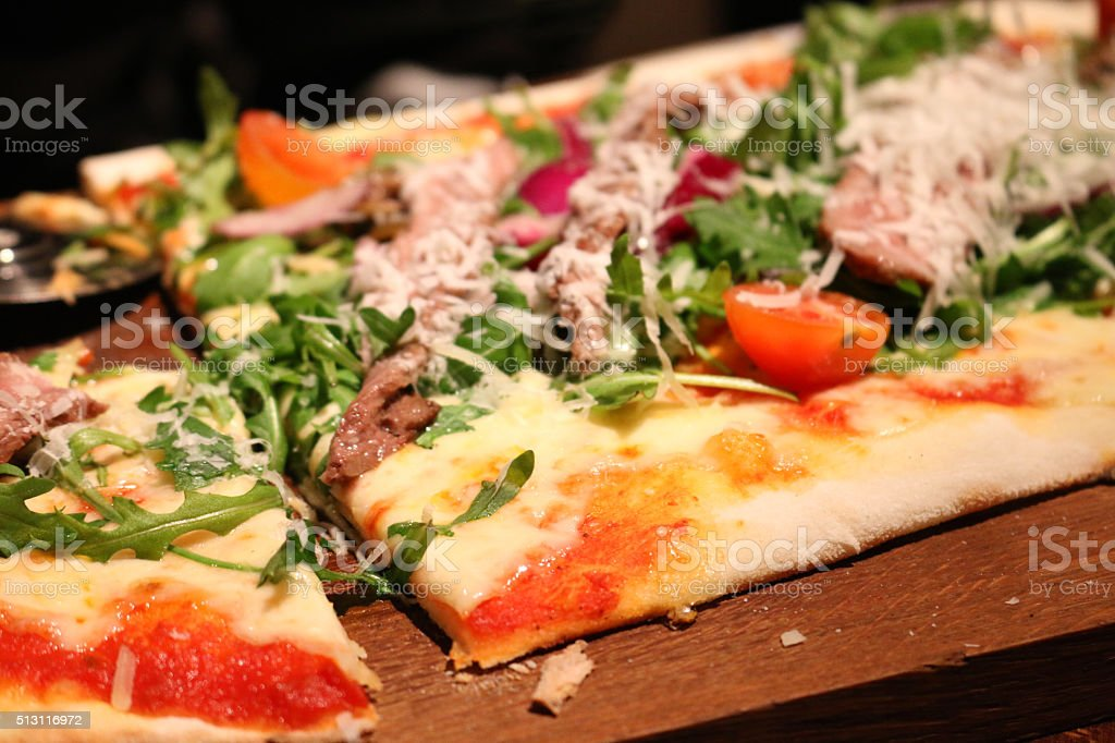 Image of pizza served on wooden bread board, salad rocket-leaves stock photo
