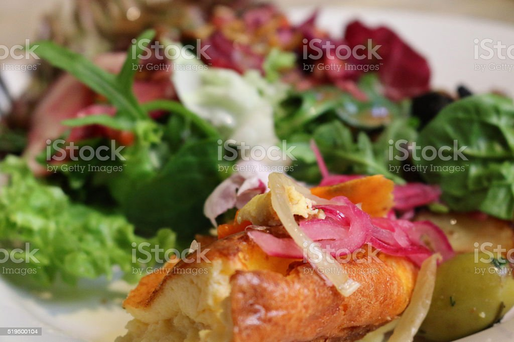 Image of plate of goat cheese souffle with side salad stock photo