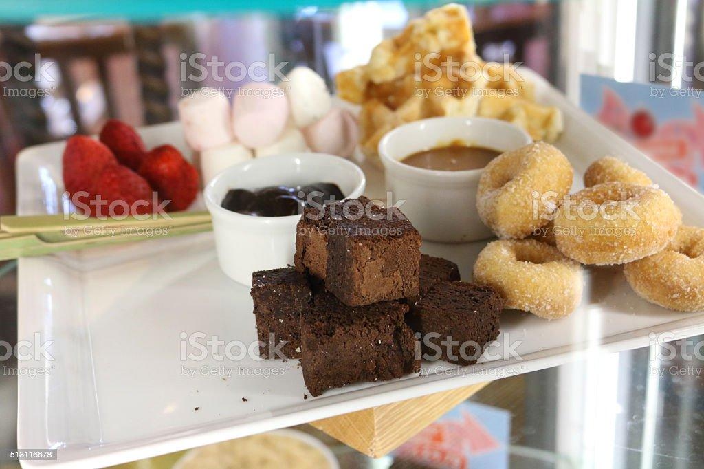 Image of pudding cabinet displaying a chocolate fondue sharing platter stock photo