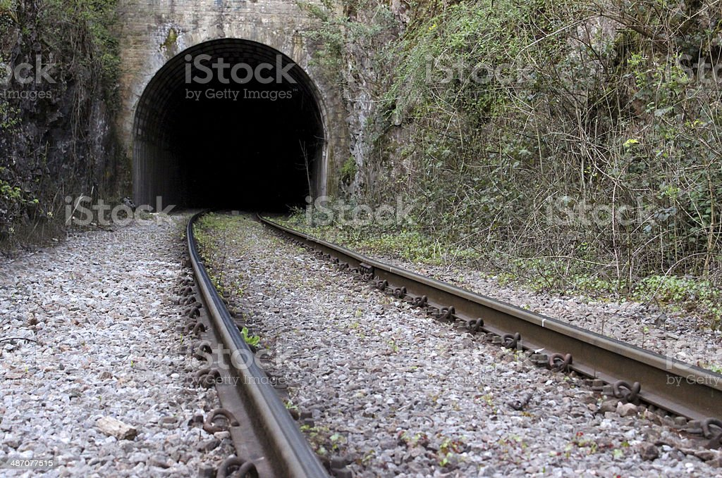 Image of rail road / railway train track disappearing into tunnel stock photo