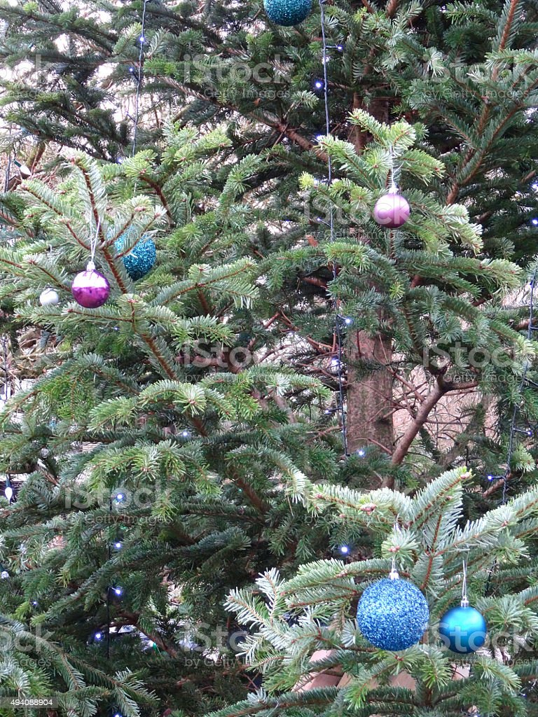 Image of real outdoor Christmas tree with decorations, baubles, fairylights stock photo