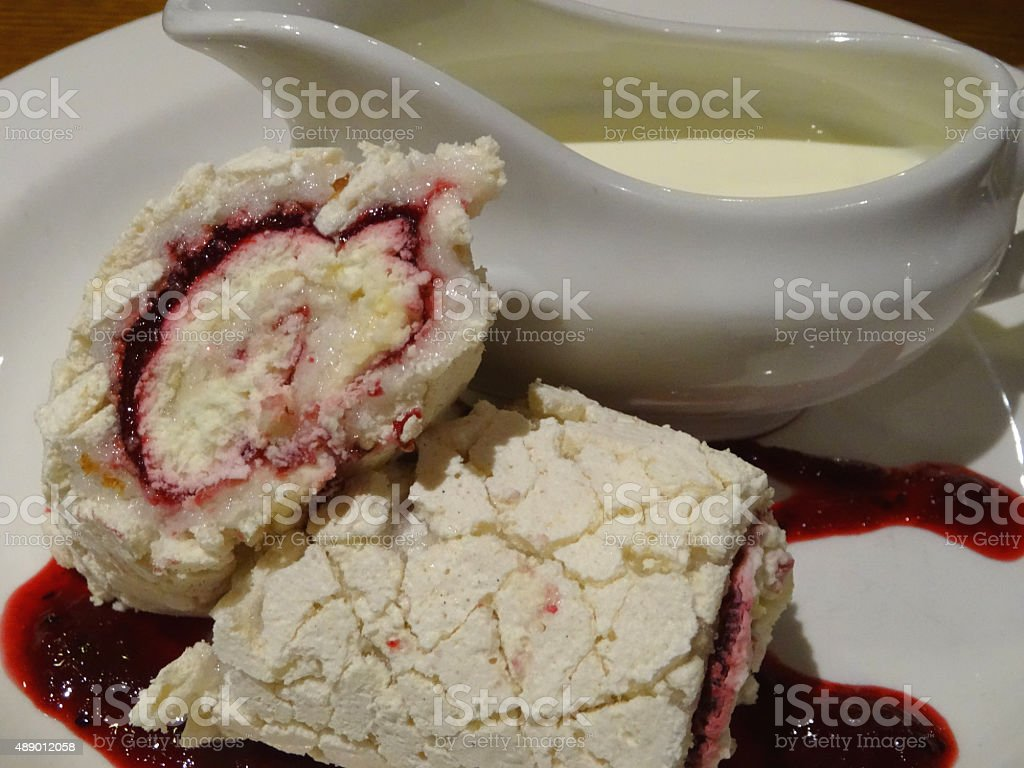Image of red berry roulade meringue cake with jug of-cream stock photo
