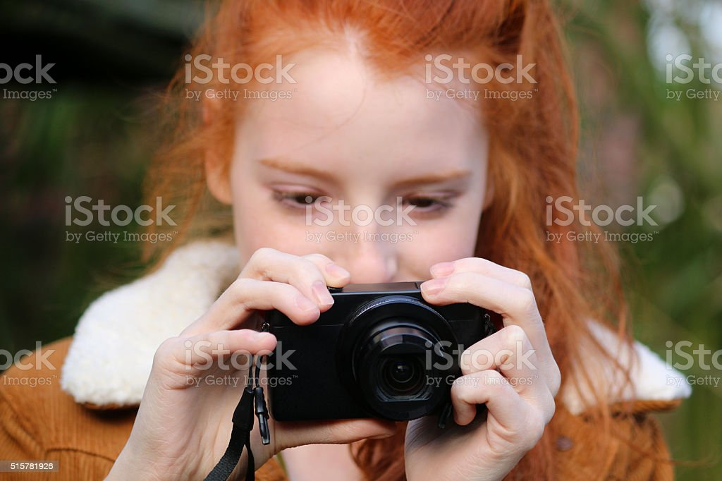 Image of redheaded female taking photos with compact digital-camera, woods stock photo