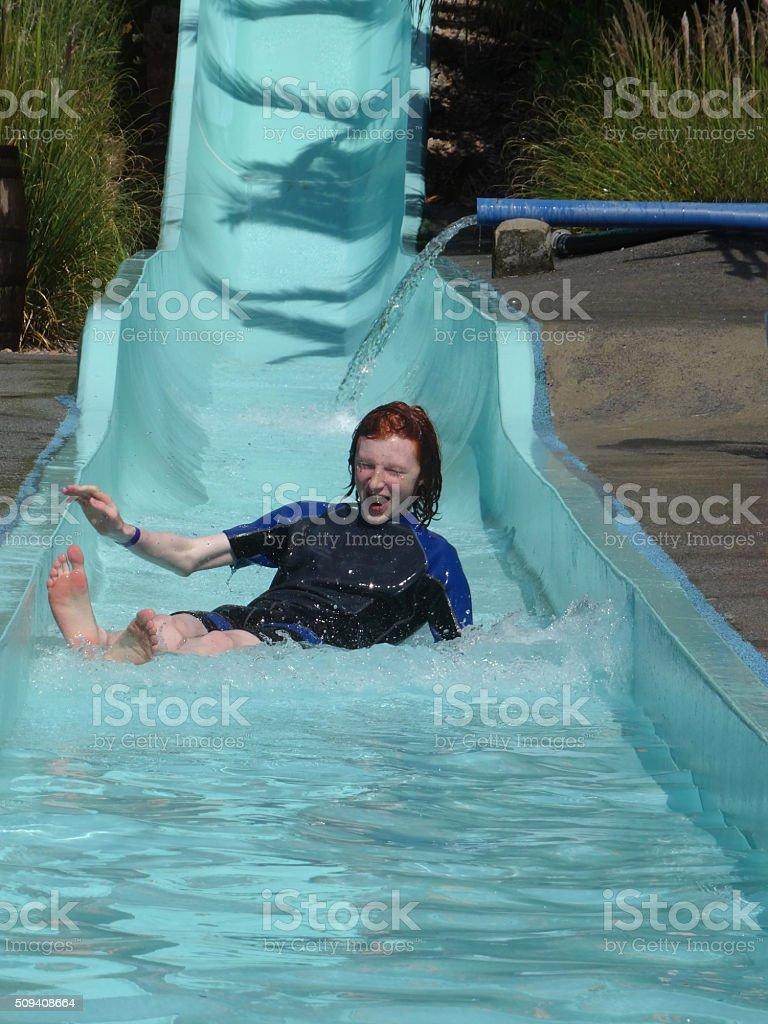 Image of redheaded teenage boy sliding down waterslide, amusement park stock photo