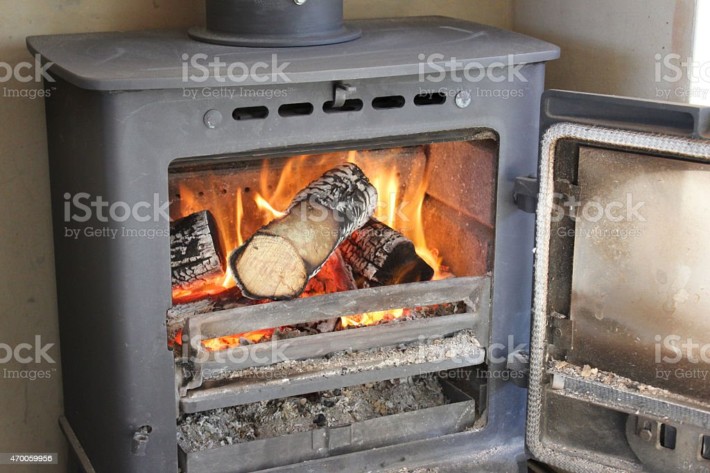 Image of roaring fire / flames, wood-burning multi-fuel stove / fireplace, door-open stock photo