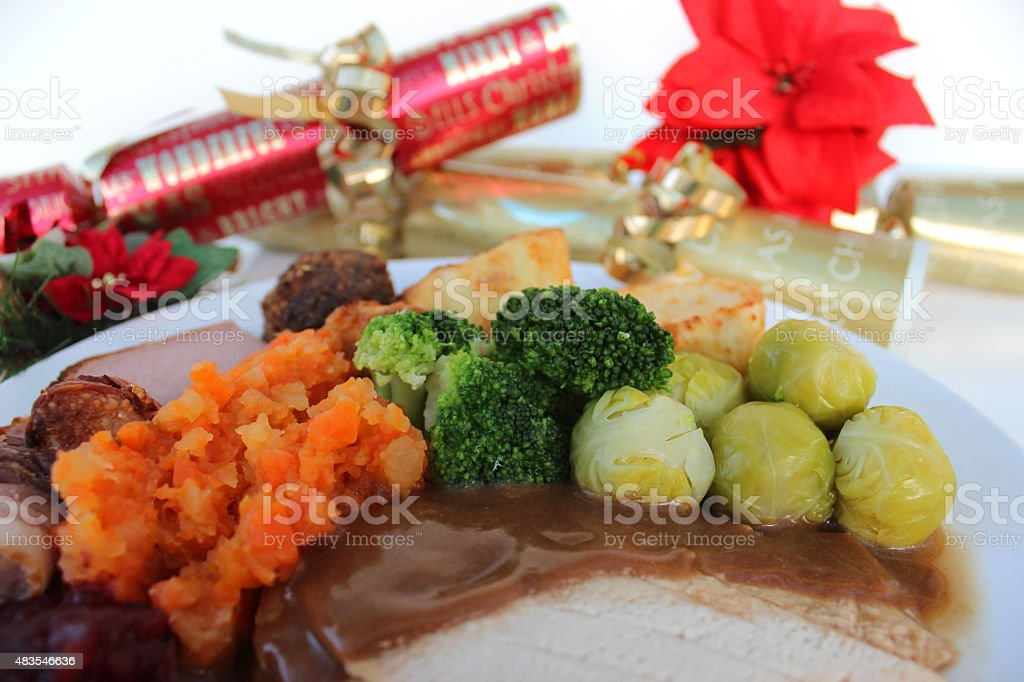 Image of roast turkey dinner with Christmas crackers, potatoes, sprouts stock photo