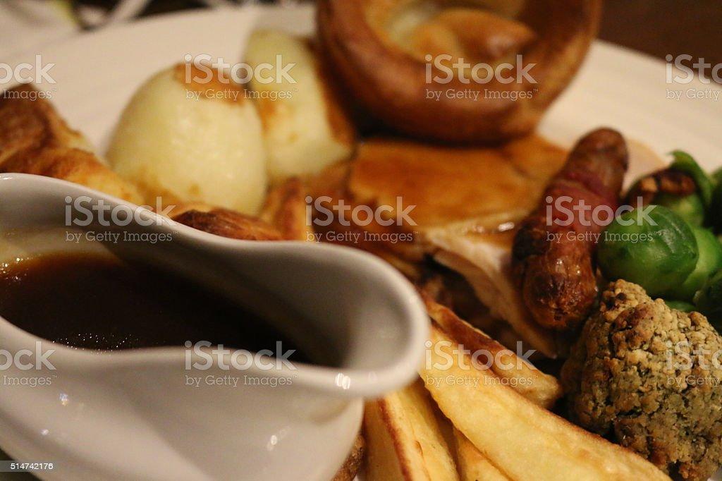 Image of roasted beef Sunday dinner, Yorkshire puddings with gravyboat stock photo
