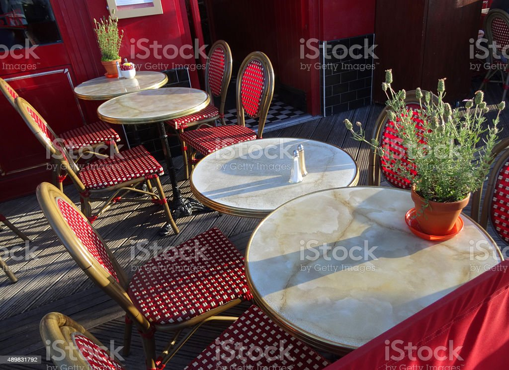 Image of round marble bistro tables and rattan chairs, French-restaurant stock photo