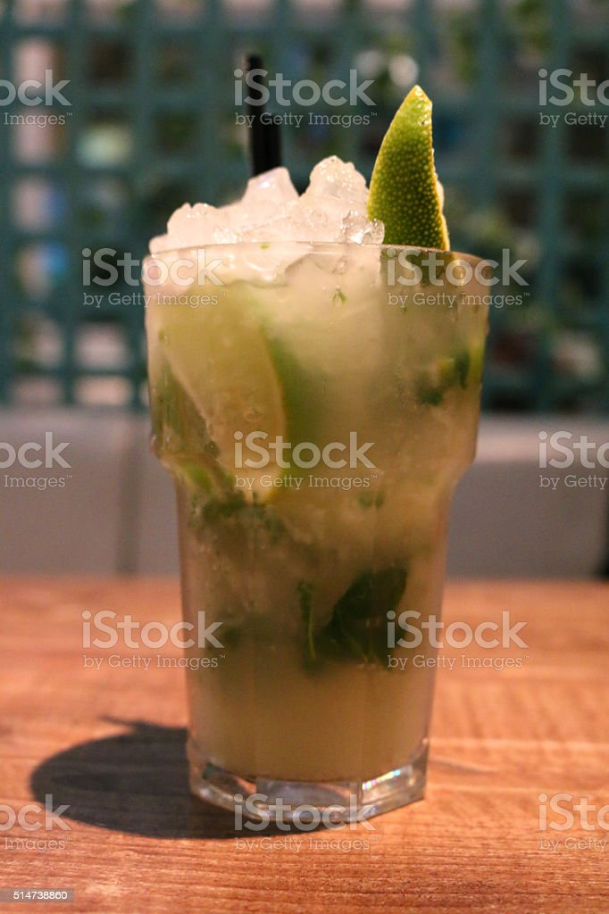 Image of rum-based alcoholic cocktail (mojito) on bar table, lime-wedge stock photo