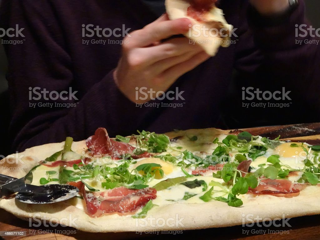Image of rustic ham and egg pizza with spinach leaves stock photo