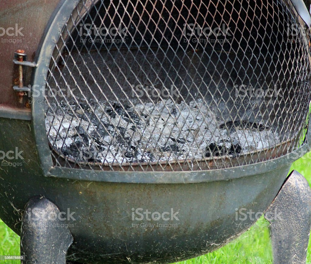 Image of rusty iron chiminea outdoor fireplace / woodburner barbecue, chimney stock photo