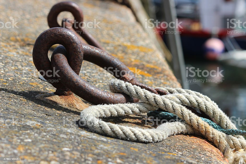 Image of rusty mooring rings on harbour wall, rope ties stock photo