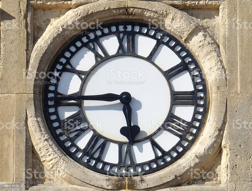 Image of sandstone clock with white clockface and Roman numerals stock photo