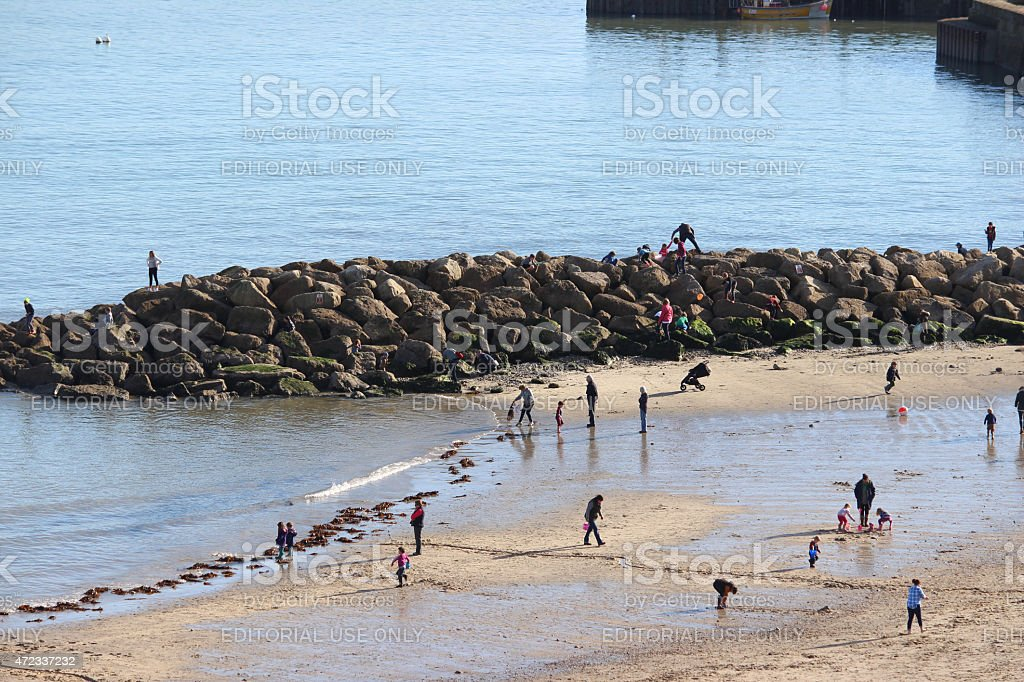 Image of sandy seaside beach with children playing in sea stock photo