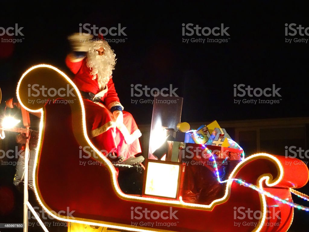 Image of Santa-Claus in sleigh with presents, waving at children stock photo