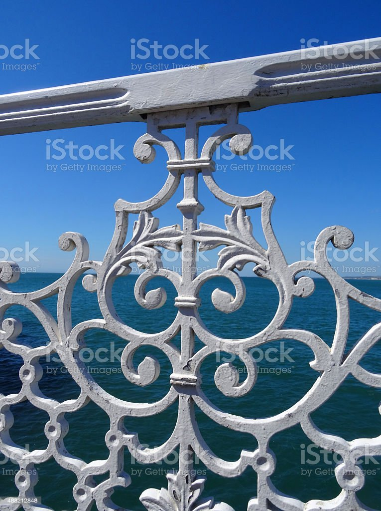 Image of seaside iron railings painted white, sea in background stock photo