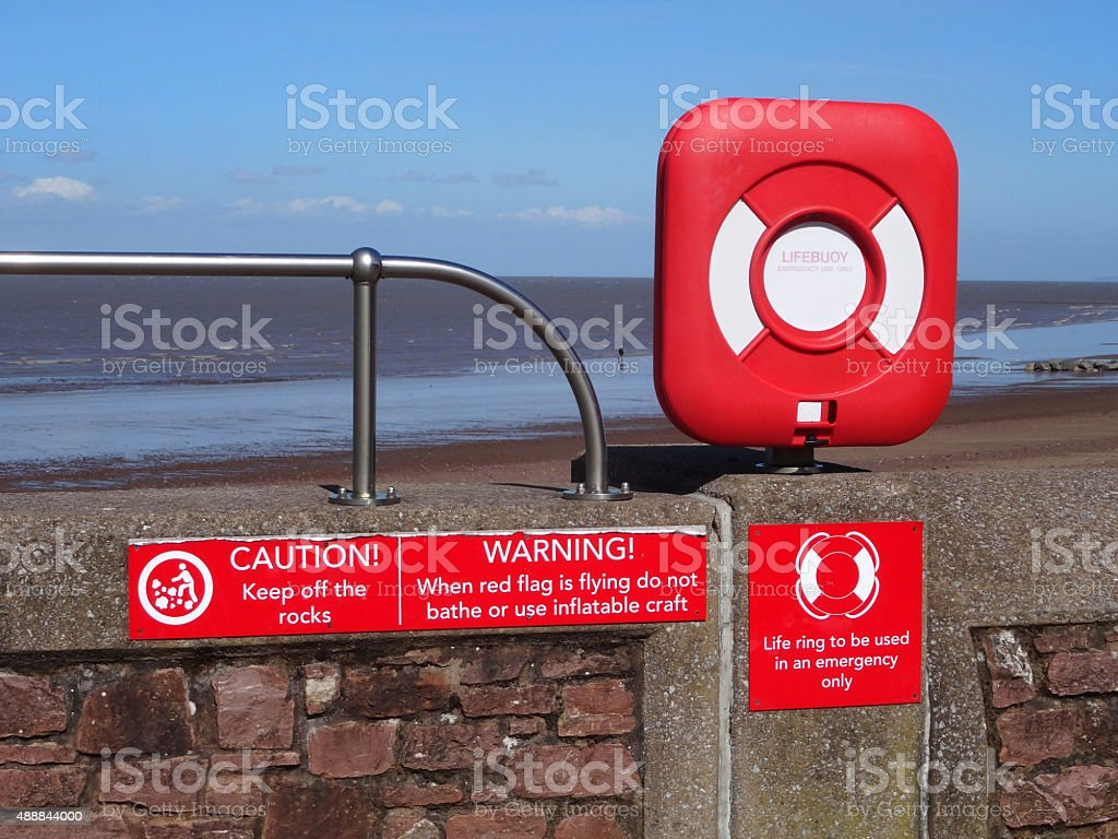 Image of seaside lifebuoy / lifering donut buoyancy aid by beach stock photo