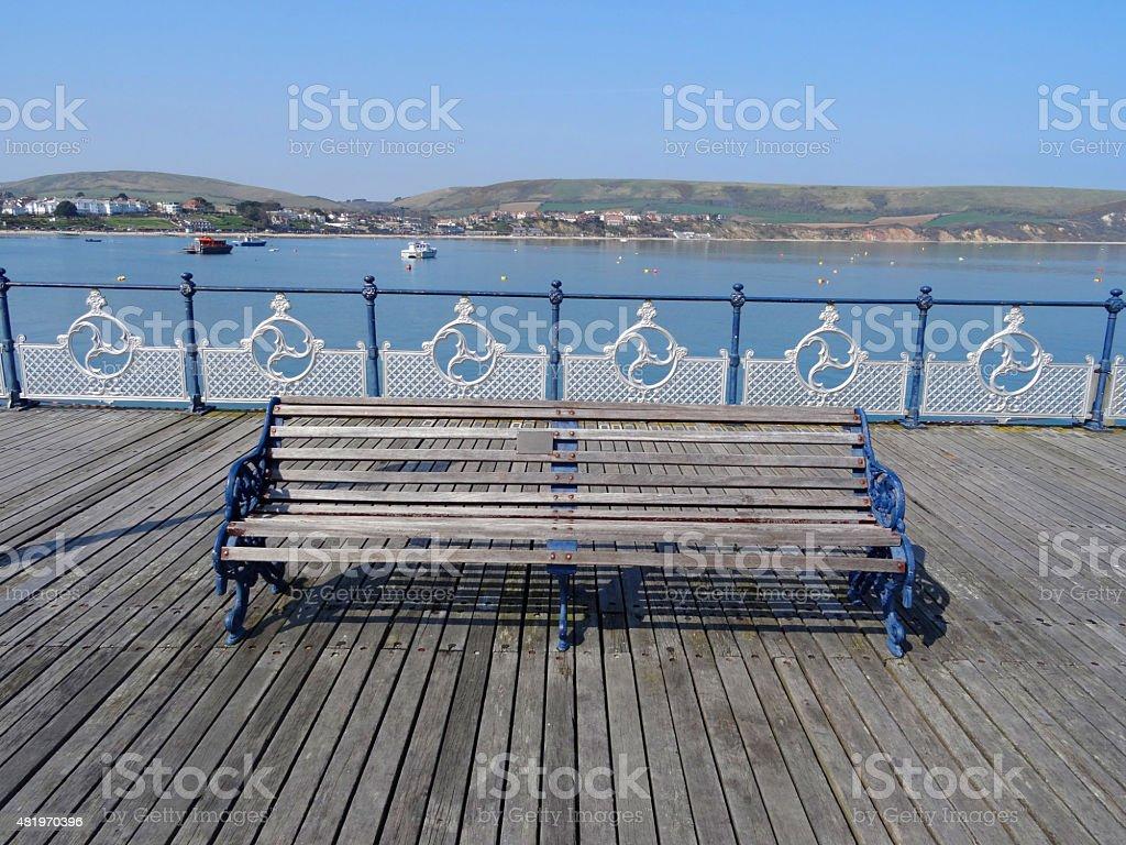 Image of seaside pier with ornamental metal bench, balustrading, decking stock photo