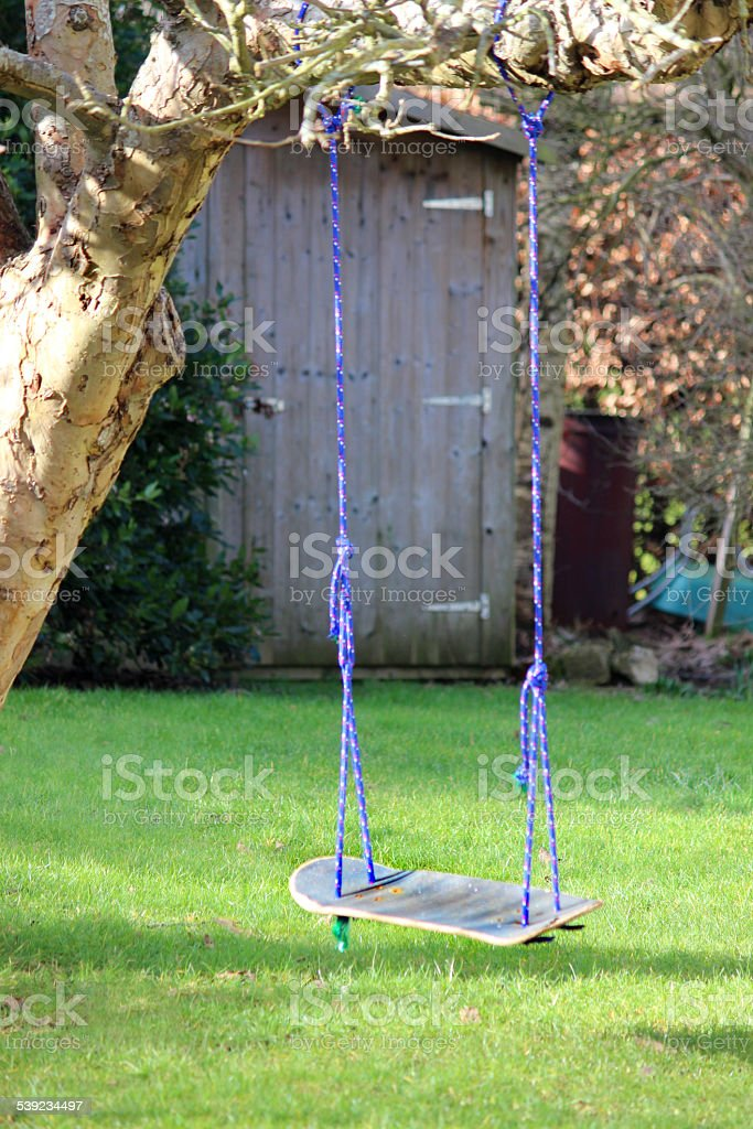 Image of skateboard swing tied to garden tree, recycling project stock photo