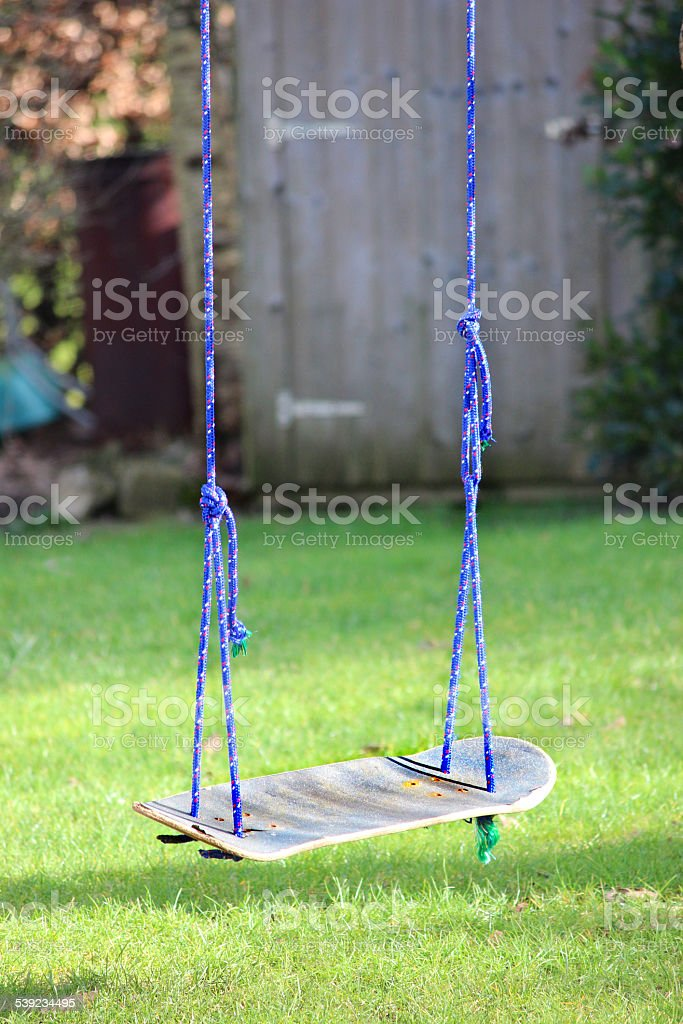 Image of skateboard swing tied to garden tree, upcycling project stock photo