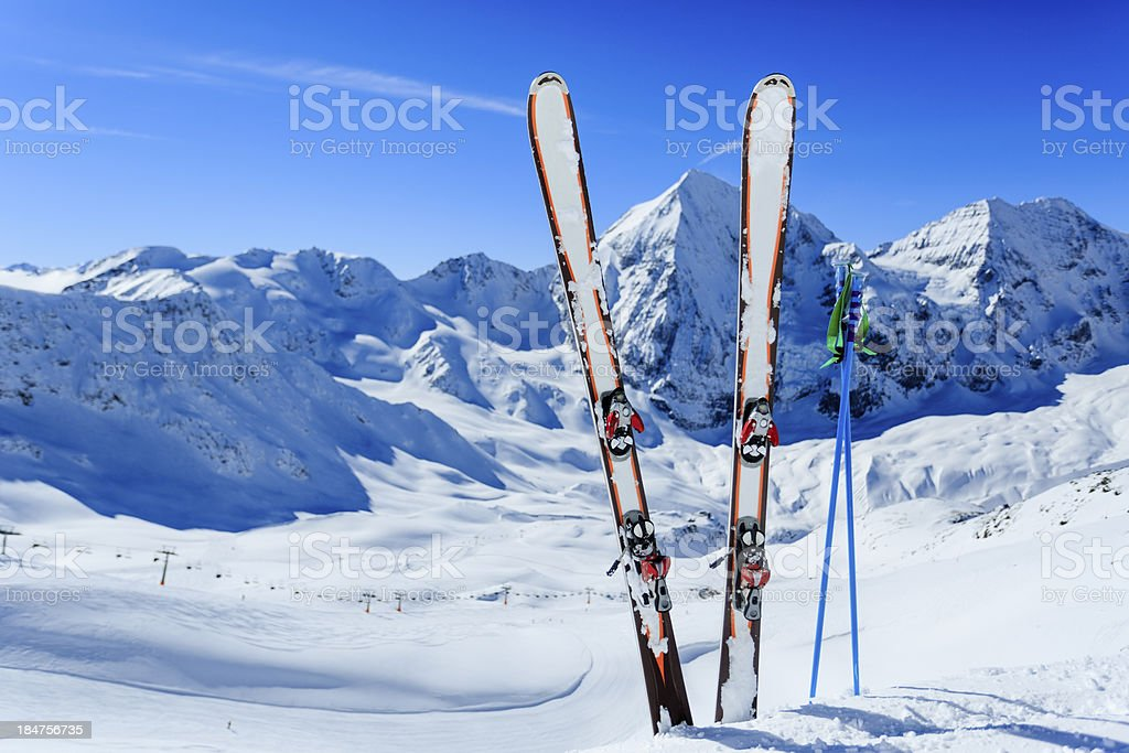 Image of ski gear stuck in snow against mountain backdrop stock photo