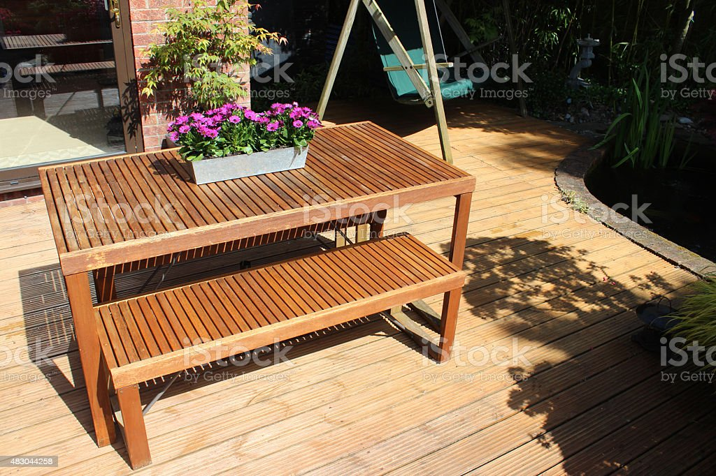 Image of slatted wooden garden-furniture, table and benches on decking stock photo