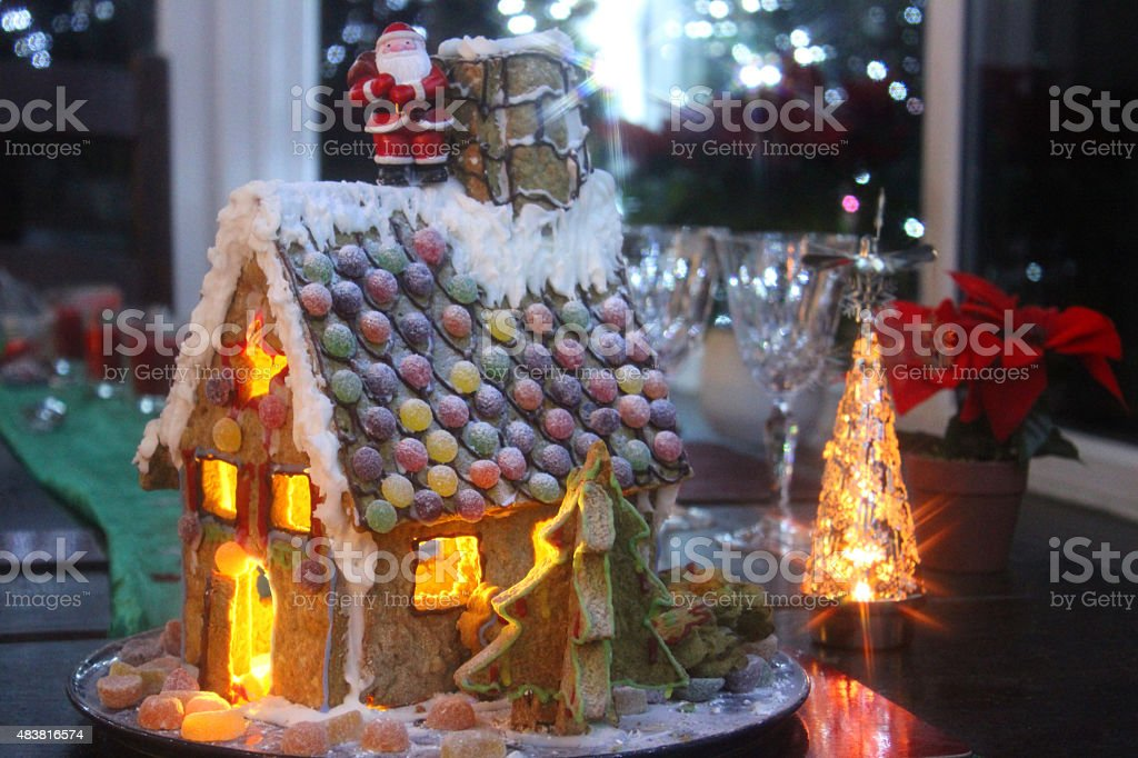 Image of small gingerbread house at Christmas-time, with nightlight candles stock photo