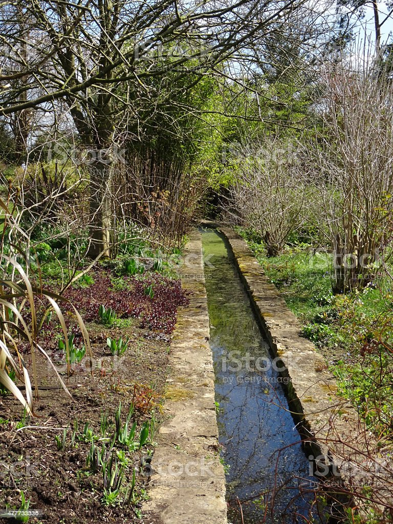 Image of stream / rill running through garden with herbaceous flowers stock photo
