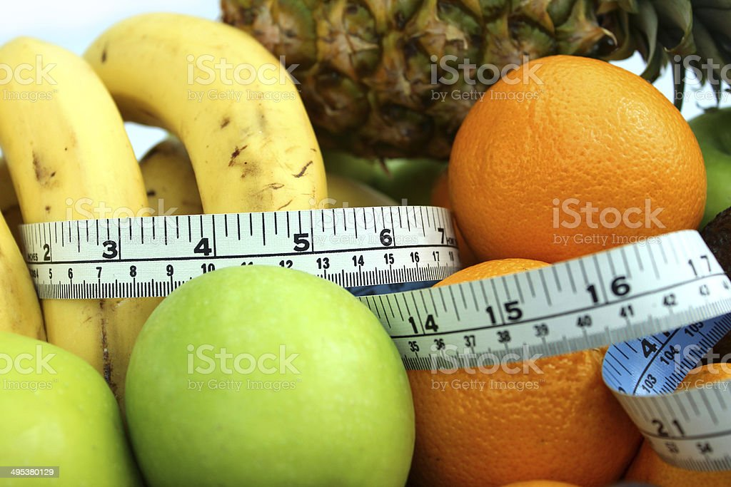 Image of tape measure with bananas, apples, oranges, pineapple, fruit stock photo