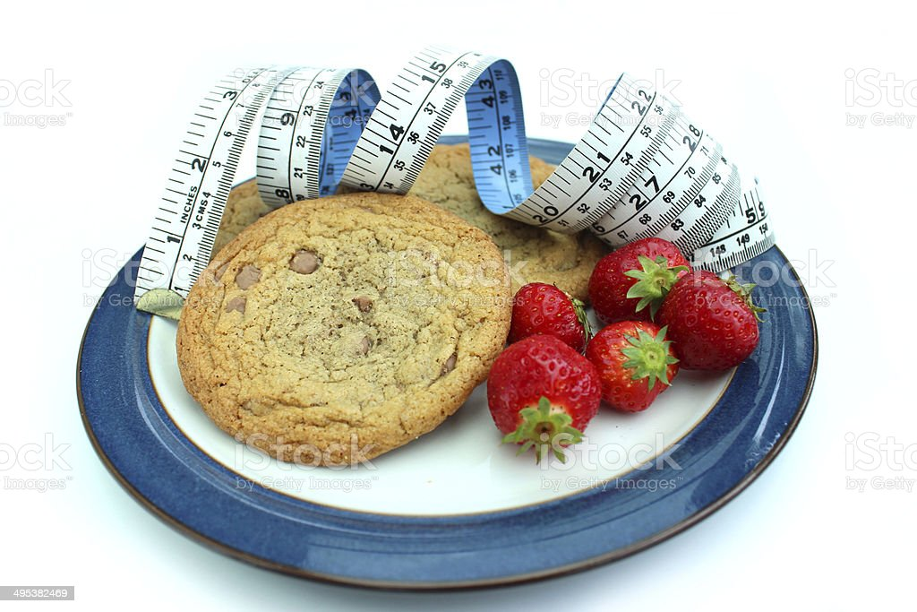 Image of tape measure with chocolate chip cookies and strawberries stock photo