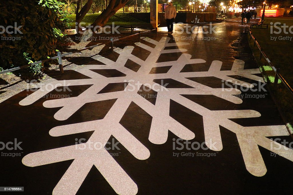 Image of tarmac footpath illuminated by festive, snowflake-design, light projection stock photo