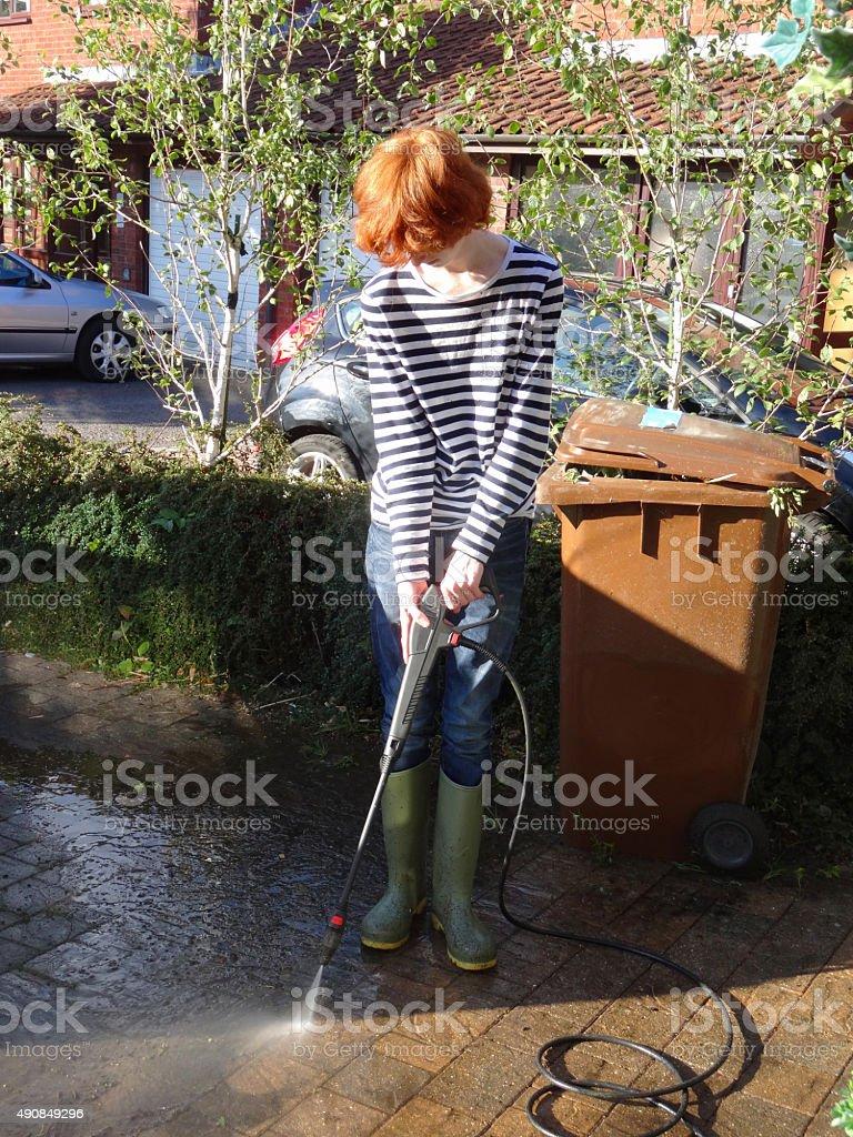 Image of teenage boy pressure-washing paved drive with powerwasher spray stock photo