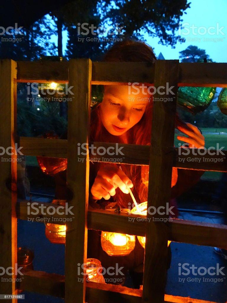 Image of teenage girl lighting tealights, jam-jars on wooden framework stock photo