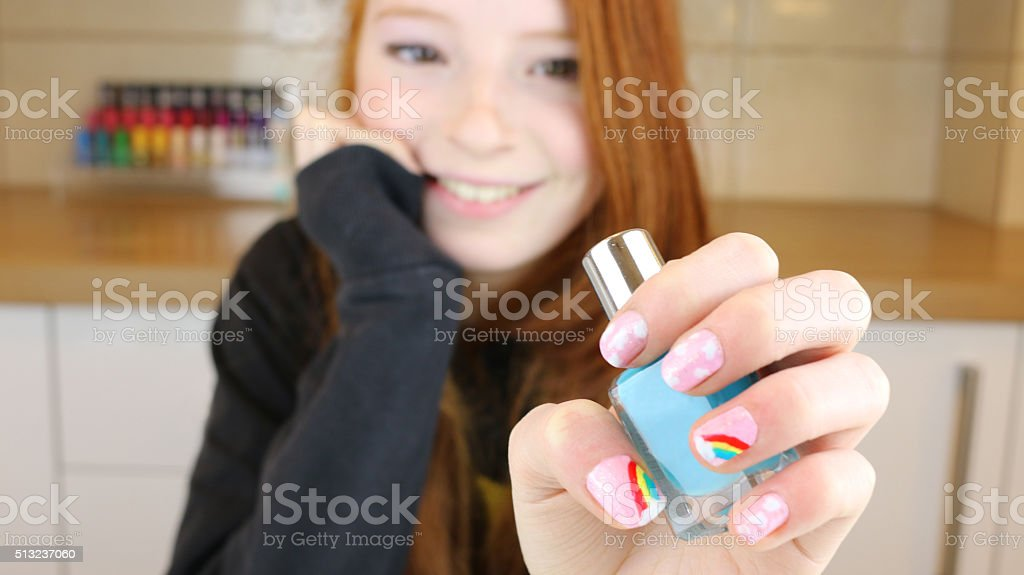 Image of teenage girl's fingernails painted with rainbows and clouds stock photo