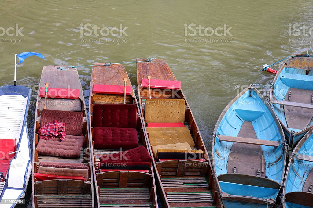 Image of tethered wooden punts and row boats on river stock photo
