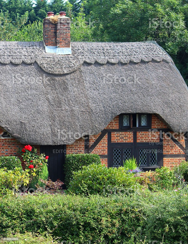 Image of thatched cottage window and garden, diagonal lead windows stock photo