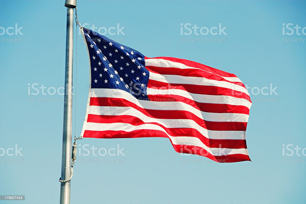 Image of the American flag against the blue sky  stock photo