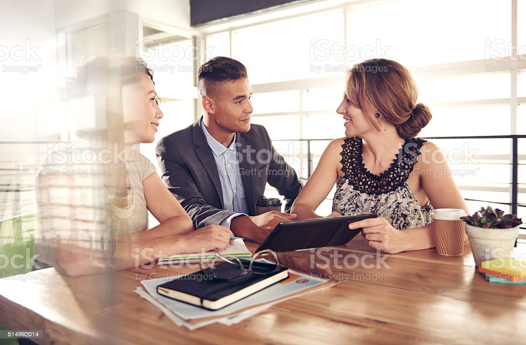 Image of three succesful business people using a tablet during stock photo