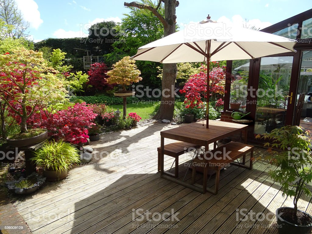 Image of timber decking, garden table with parasol, UPVC-conservatory, maples stock photo