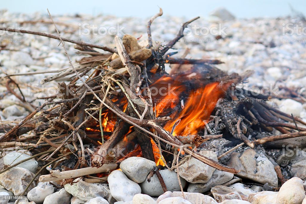 Image of tinder and kindling of beach bonfire, sea background stock photo