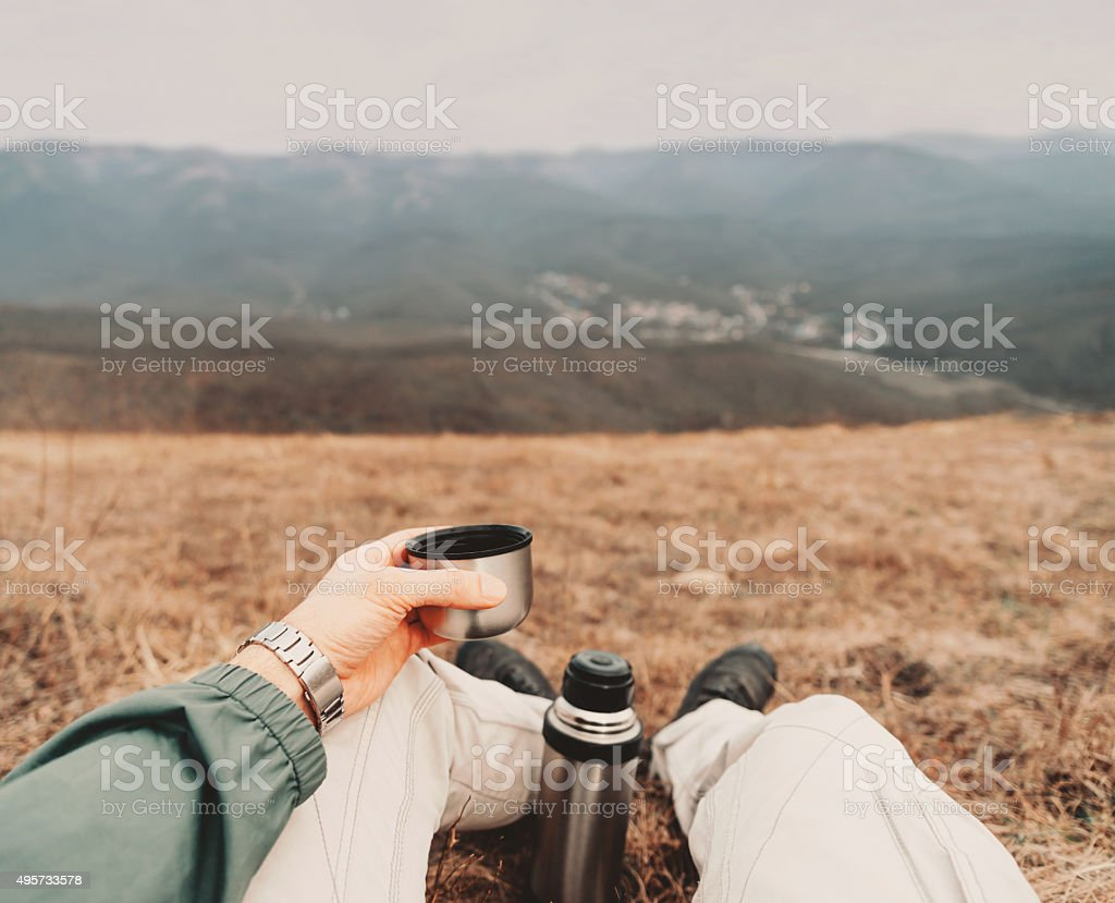 POV image of traveler with thermos stock photo