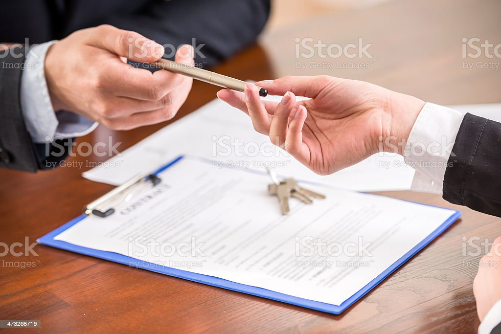 Image of two realtors sharing a pen stock photo