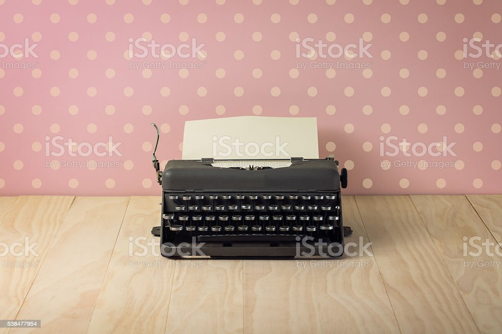 Image of vintage typewriter on pink polka dots wallpaper stock photo