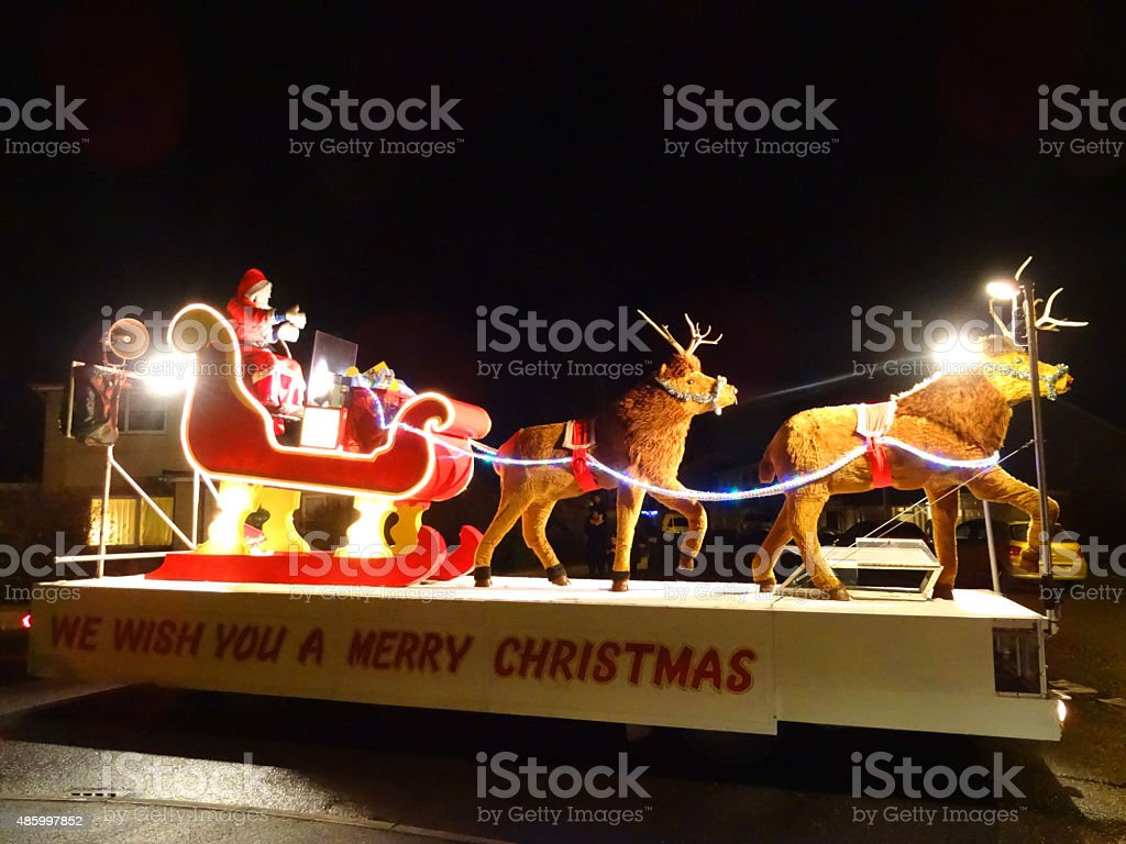 Image of waving Santa Claus on carnival-float, sitting in sleigh stock photo