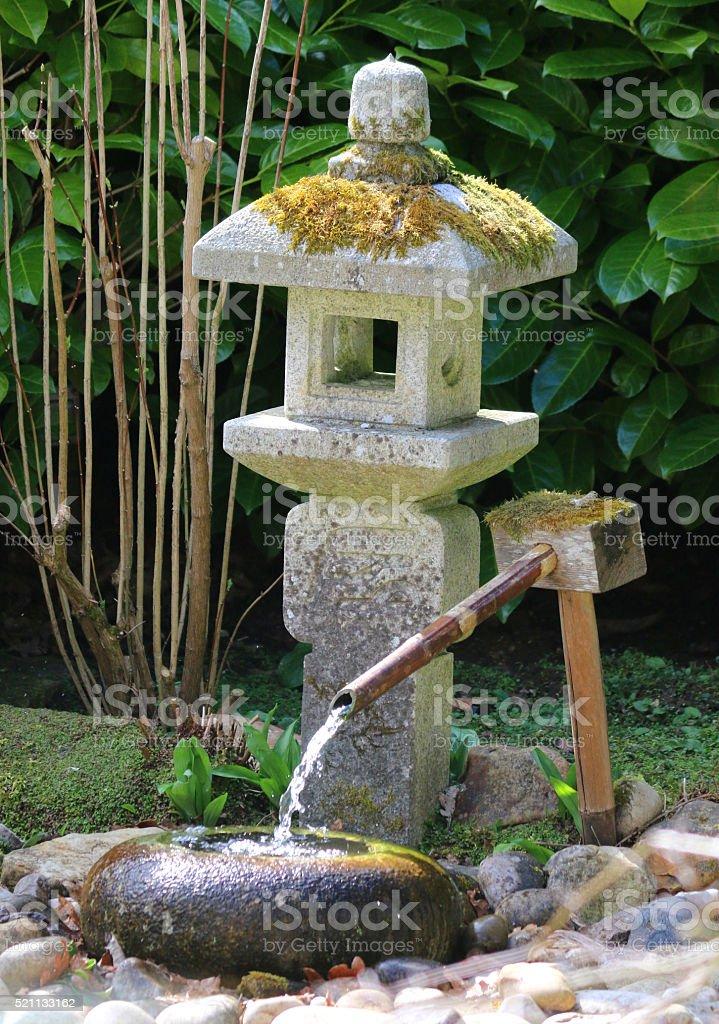 Image of weathered granite Japanese lantern , water basin, deer scarer stock photo