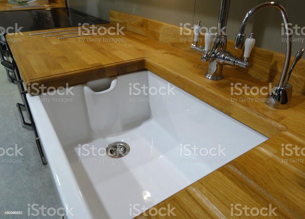 Image of white ceramic Belfast butler sink, wooden kitchen worktop stock photo