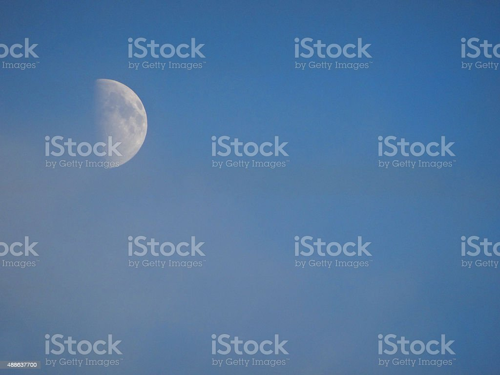 Image of white half moon in afternoon clear blue sky stock photo